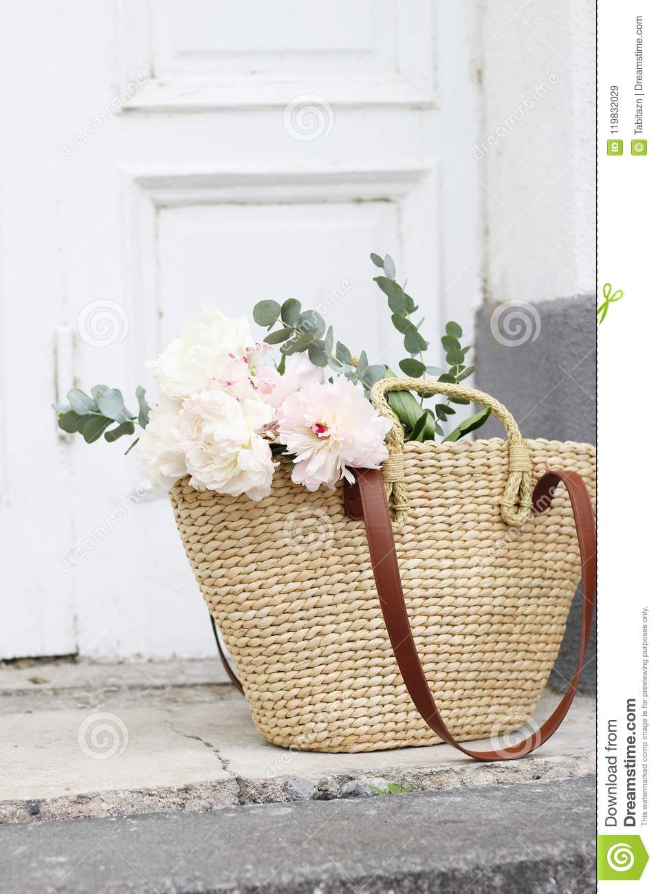 Styled stock photo. Feminine wedding still life composition with straw French basket bag with pink peonies flowers and