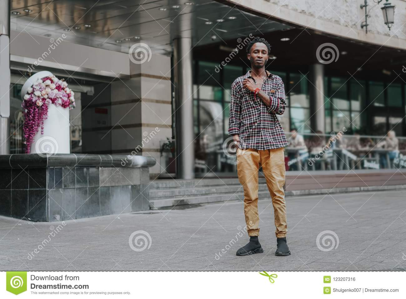 Stylish african american boy on the plaid shirt. Trendy hipster and rapper posed at street. Fashionable black guy. A student walks
