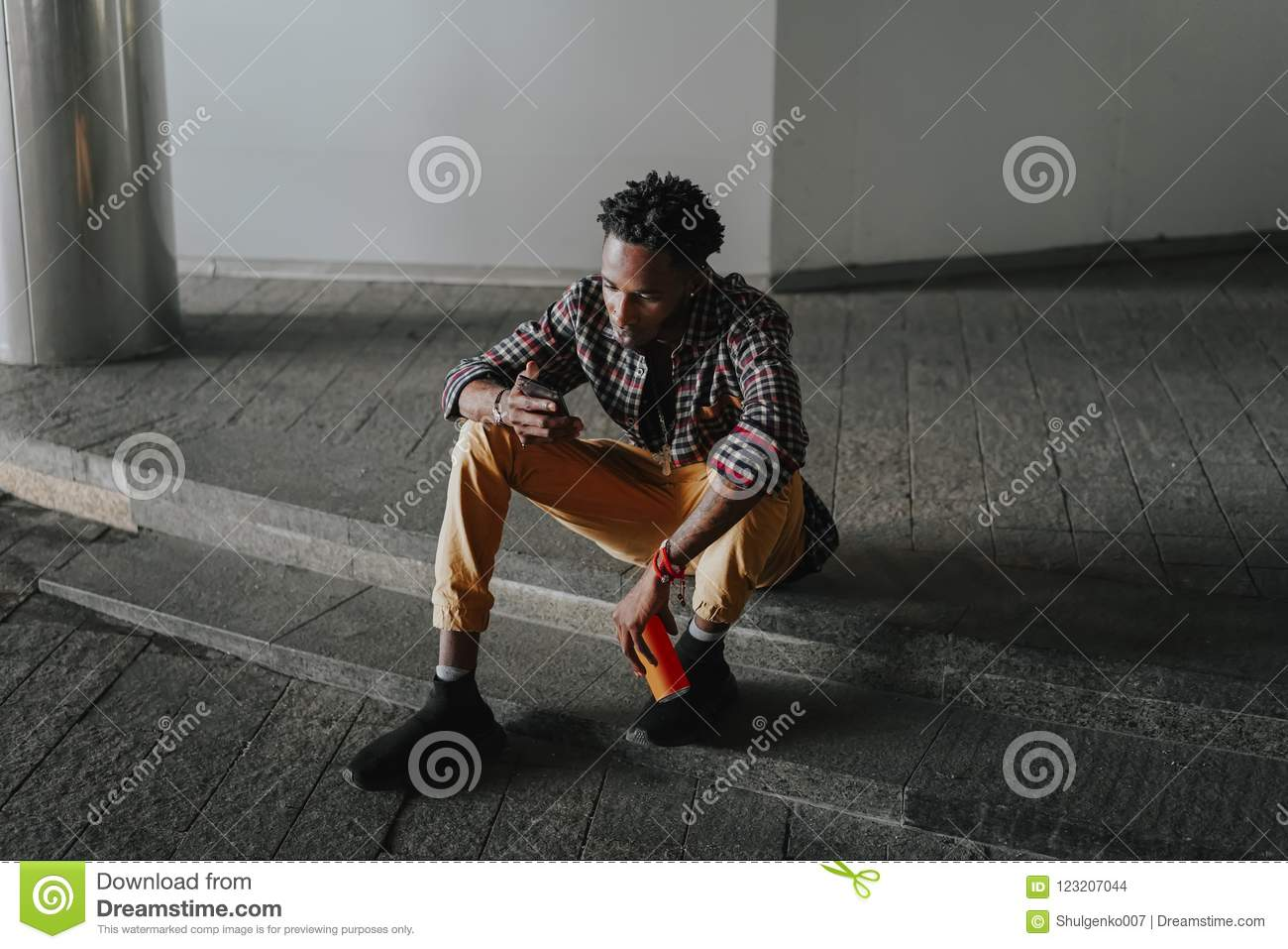 Stylish african american boy on the plaid shirt. Trendy hipster and rapper posed at street sitting with mobile phone and can of so