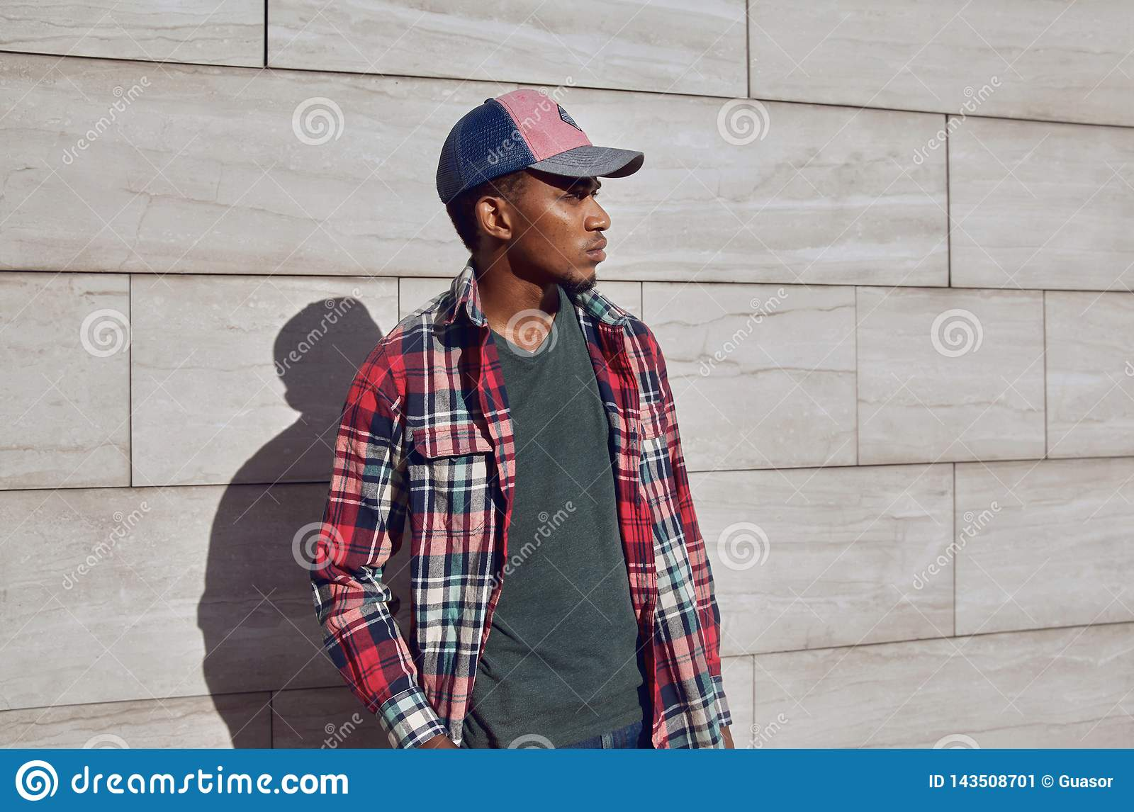 Stylish african man wearing red plaid shirt, baseball cap, looking away, young guy posing on city street, gray brick wall
