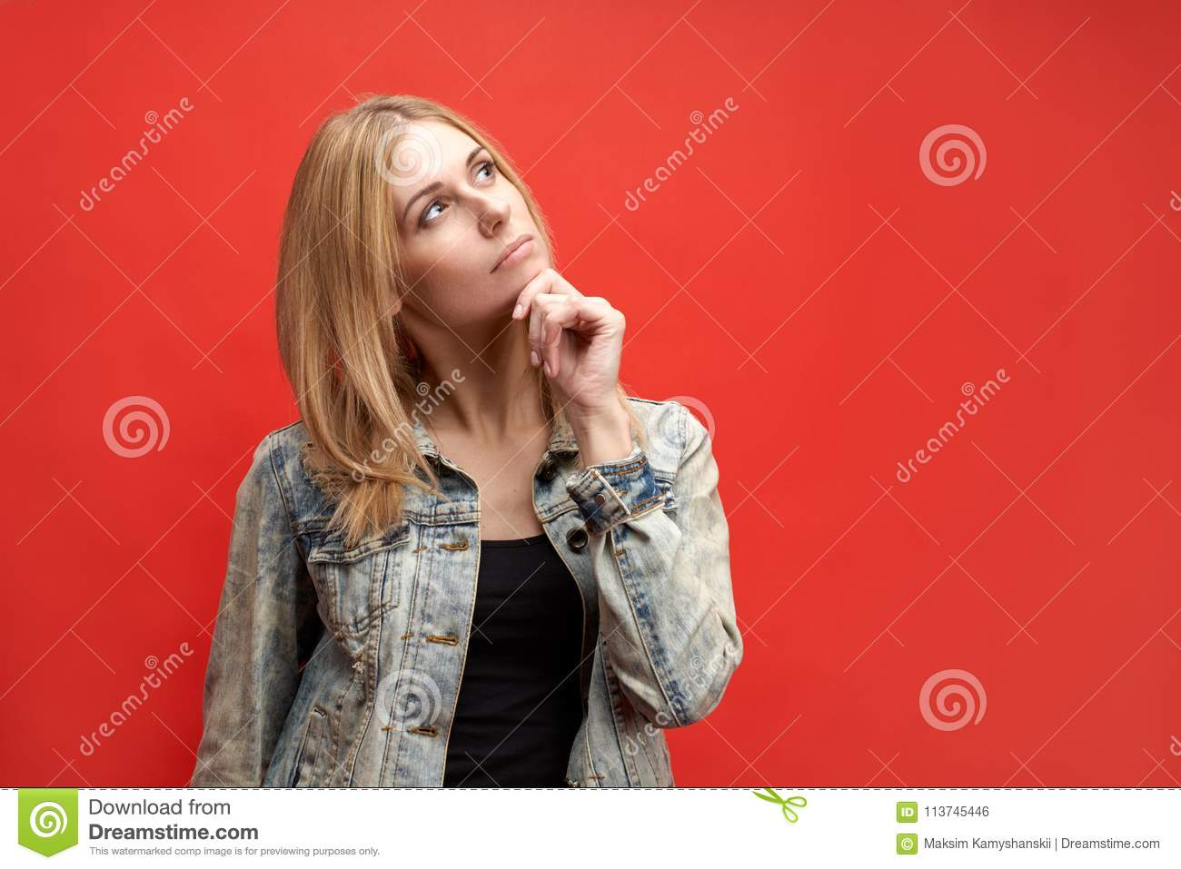 Stylish attractive slender young blonde student woman thoughtfully holds her chin and looks up with a pensive expression.