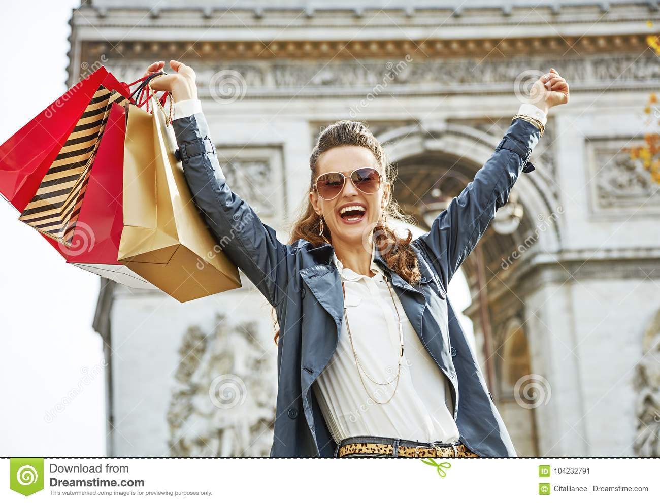 Smiling woman with shopping bags in Paris, France rejoicing