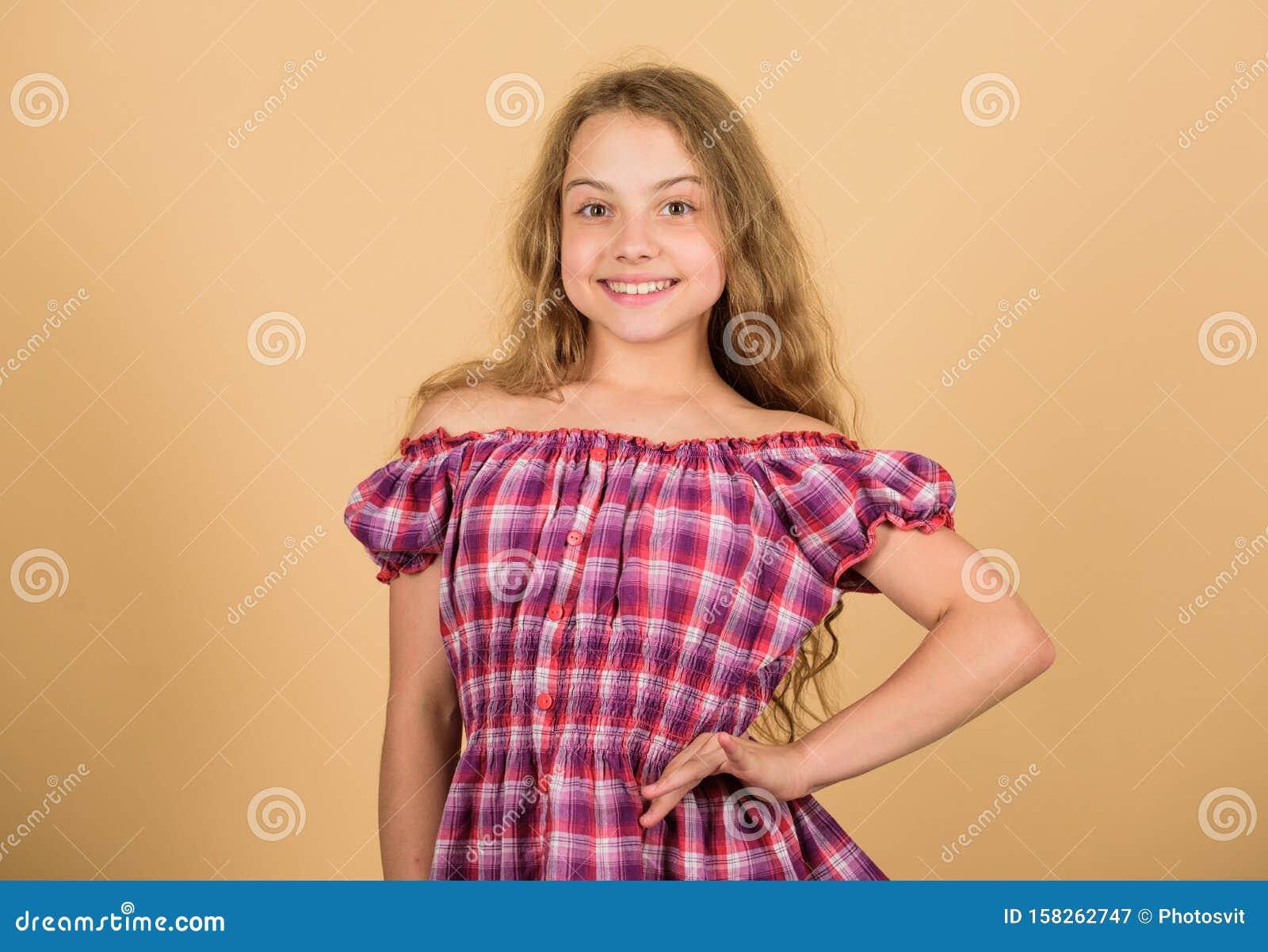 Stylish beauty. kid fashion. long blond curly hair. beautiful little girl fashion model. small kid in dress. happy small