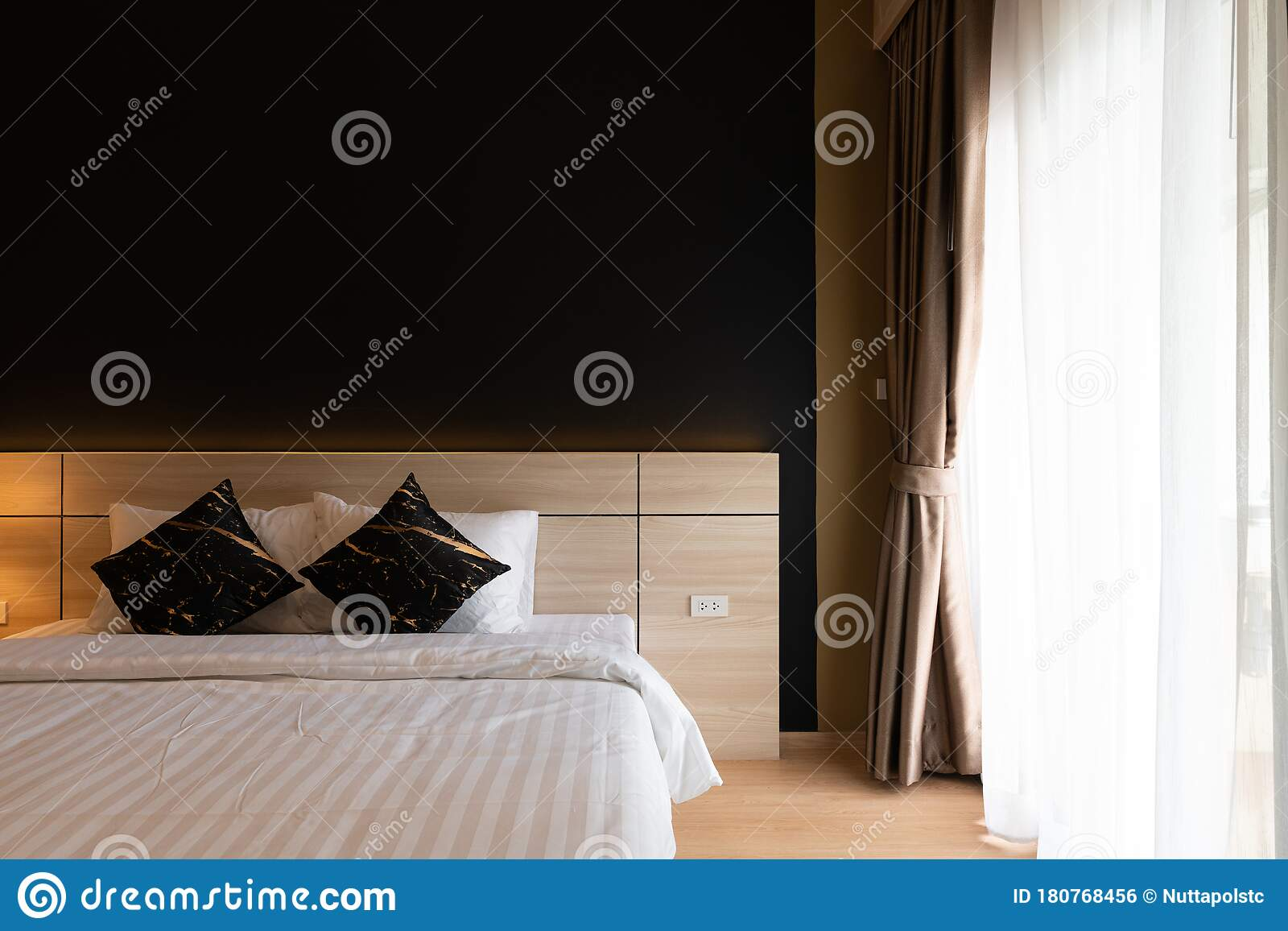 Stylish Bedroom Corner With Wooden Headboard And Bed With Soft Pillows Setting With Navy Blue Painted Wall In Natural Light Stock Photo Image Of Fabric Blanket 180768456