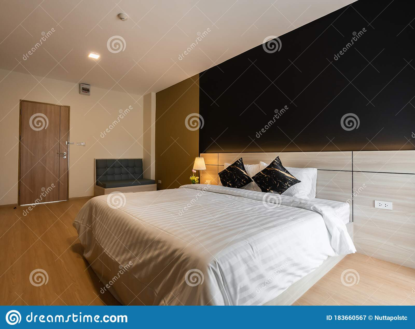 Stylish Bedroom Corner With Wooden Headboard And Bed With Soft Pillows Setting With Navy Blue And Yellow Painted Wall On The Stock Image Image Of Nice Light 183660567