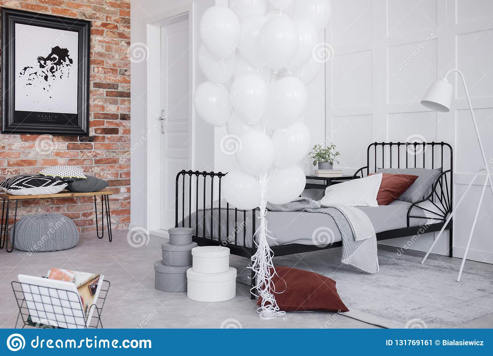 Bedroom interior with grey bedding, bunch of white balloons and black frame on the brick wall, real photo