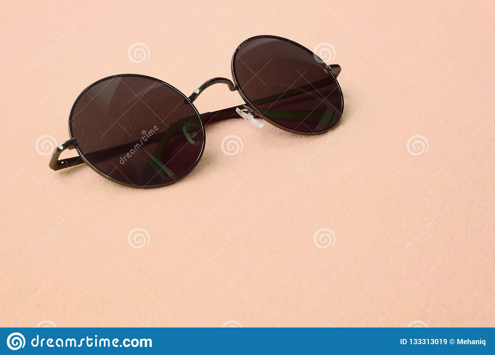 0406b0a2fd57 Stylish black sunglasses with round glasses lies on a blanket made of soft  and fluffy light orange fleece fabric. Fashionable background picture in  fashion ...
