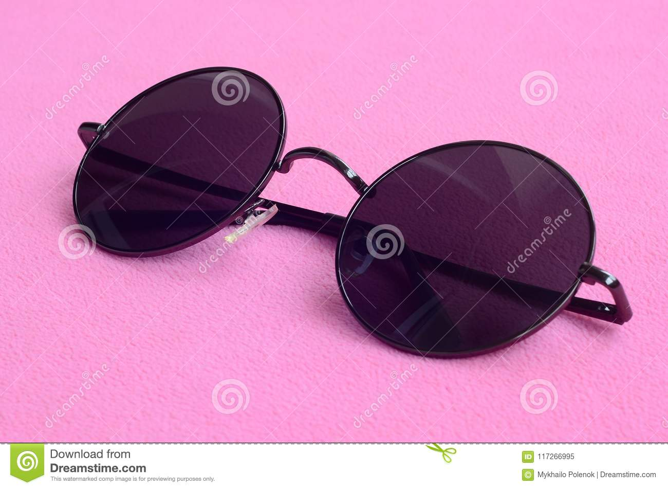 cd08f4ba68b1 Stylish black sunglasses with round glasses lies on a blanket made of soft  and fluffy light pink fleece fabric. Fashionable background picture in  female ...