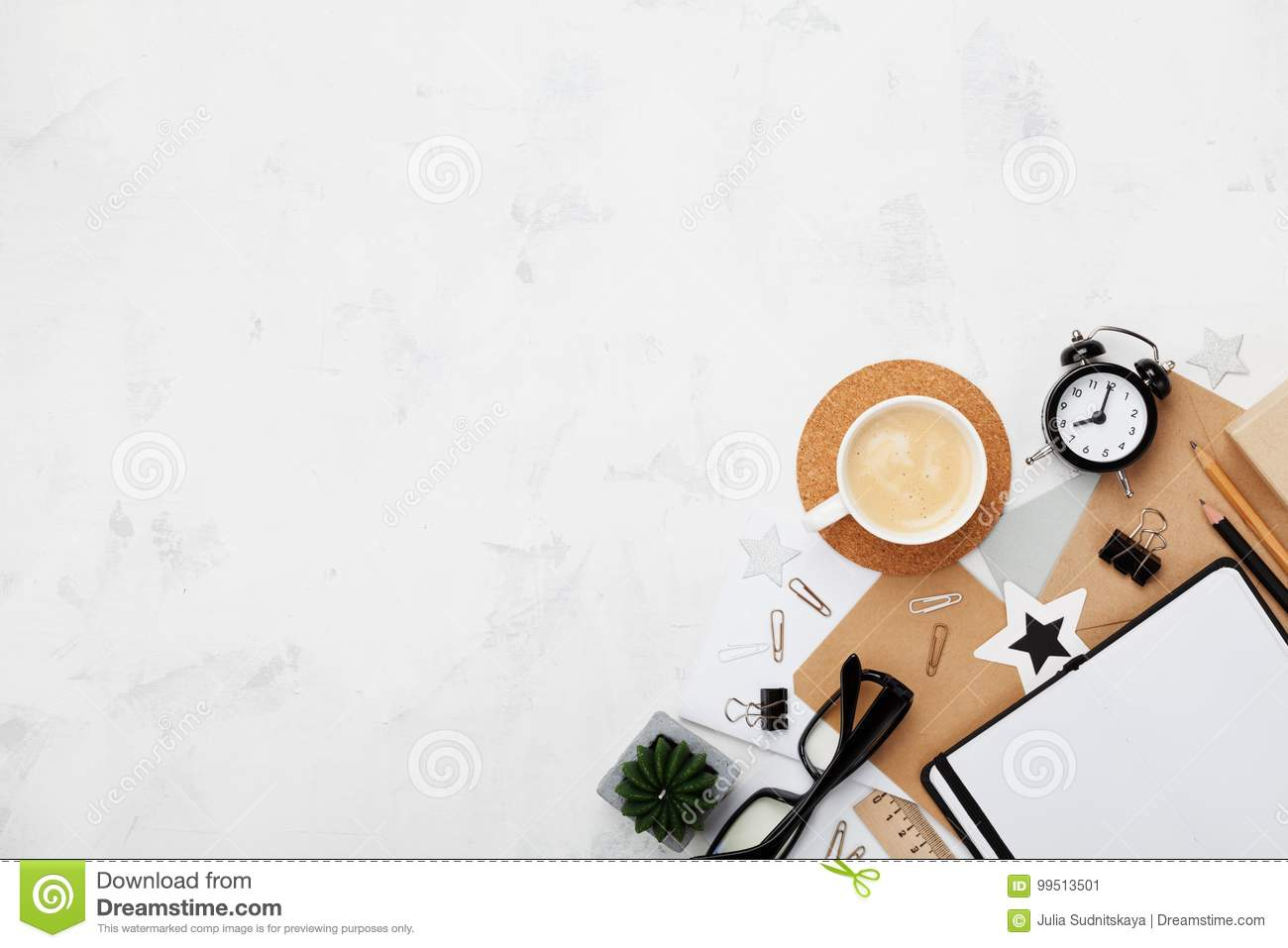 Stylish blogger working desk with coffee, office supply, alarm clock and clean notebook on white table top view. Flat lay.