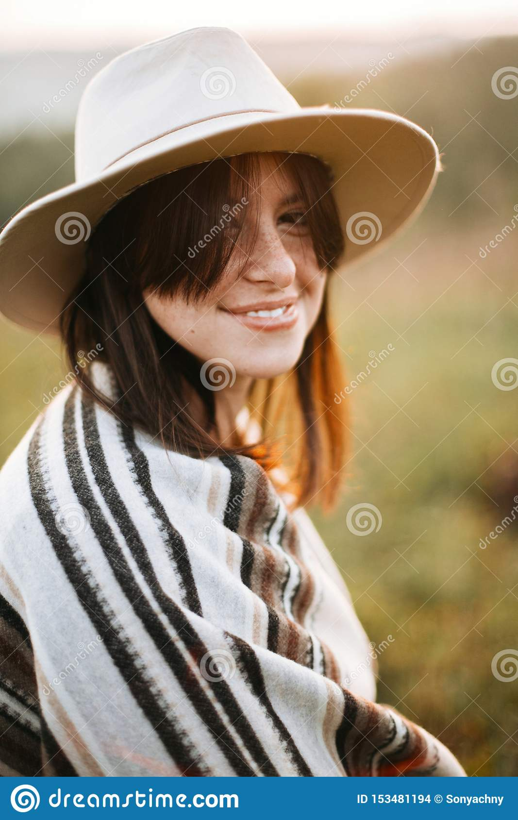 Stylish boho girl smiling in sunny light at atmospheric sunset in meadow. Happy hipster woman in poncho and hat enjoying