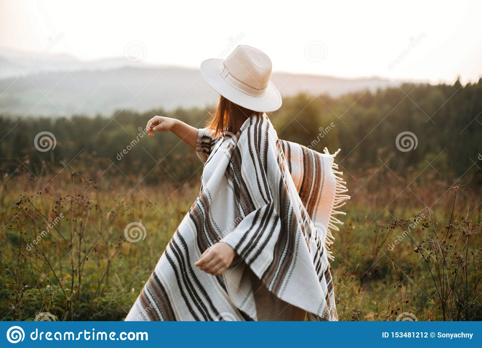 Stylish boho girl walking in sunny light at atmospheric sunset in meadow. Happy hipster woman in poncho and hat enjoying traveling