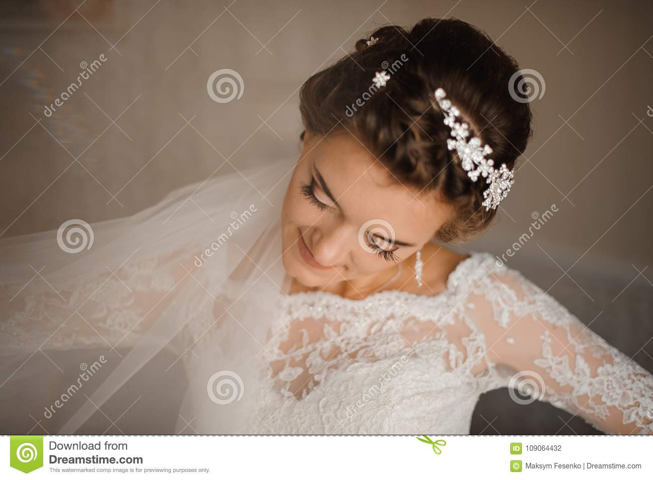 Bride in a white dress and veil is standing with her head bowed