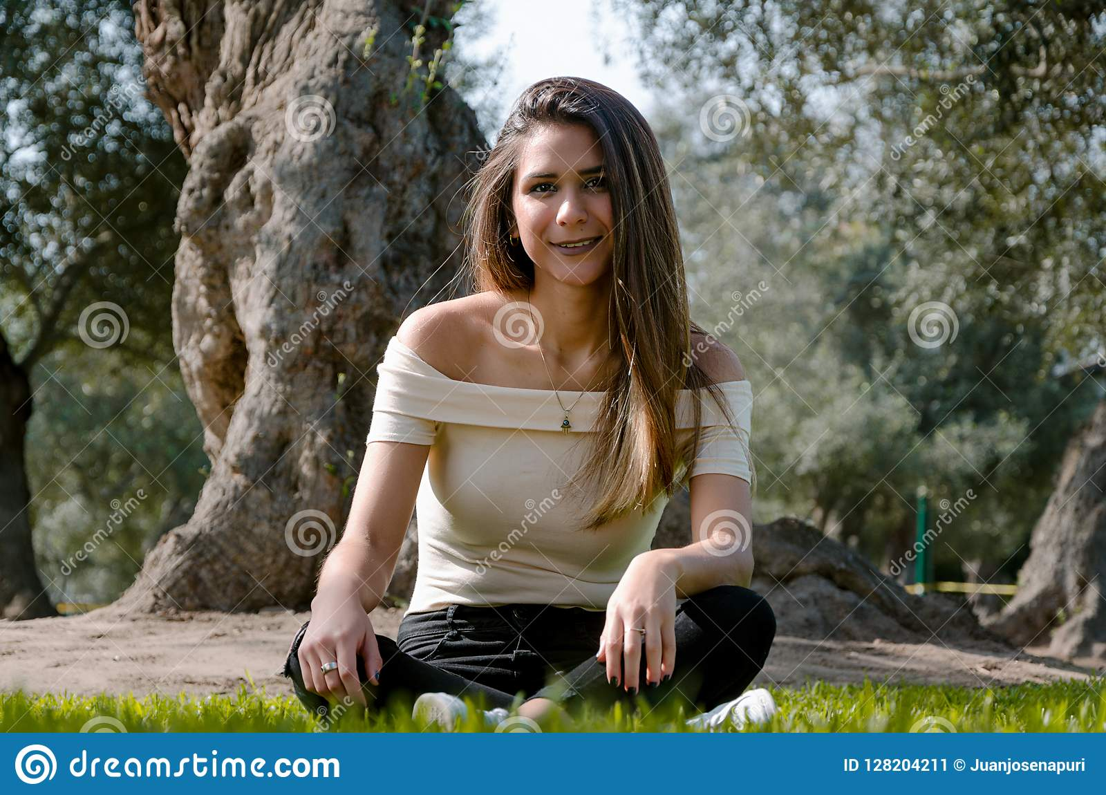 Stylish cheerful brunette sitting under a tree in a park