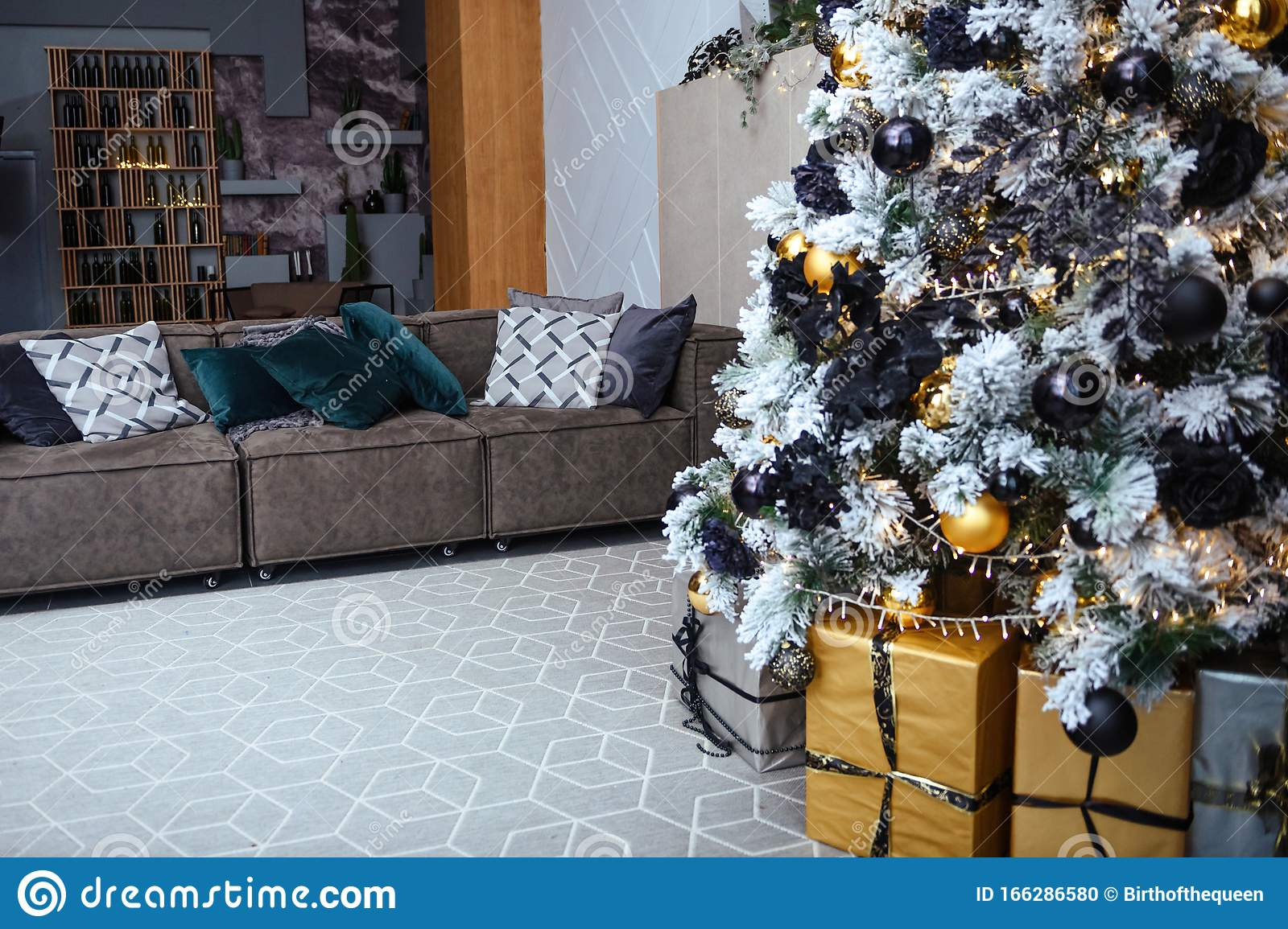 Stylish Christmas Living Room Decor In Gold And Silver Tones A Large Beautifully Decorated Christmas Tree Stands In The Room Next Stock Photo Image Of Cone Bright 166286580