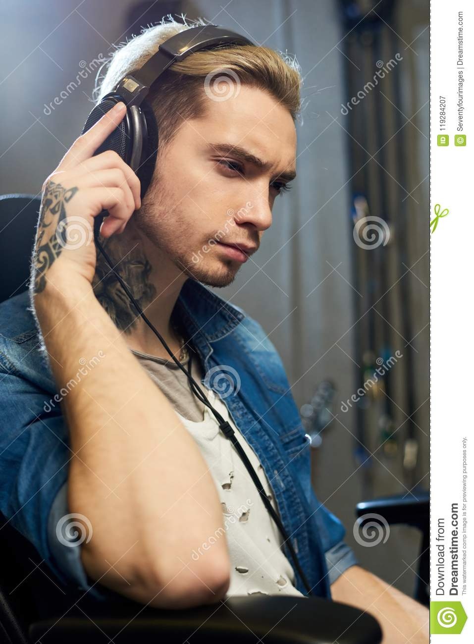 Stylish composer listening to music in studio
