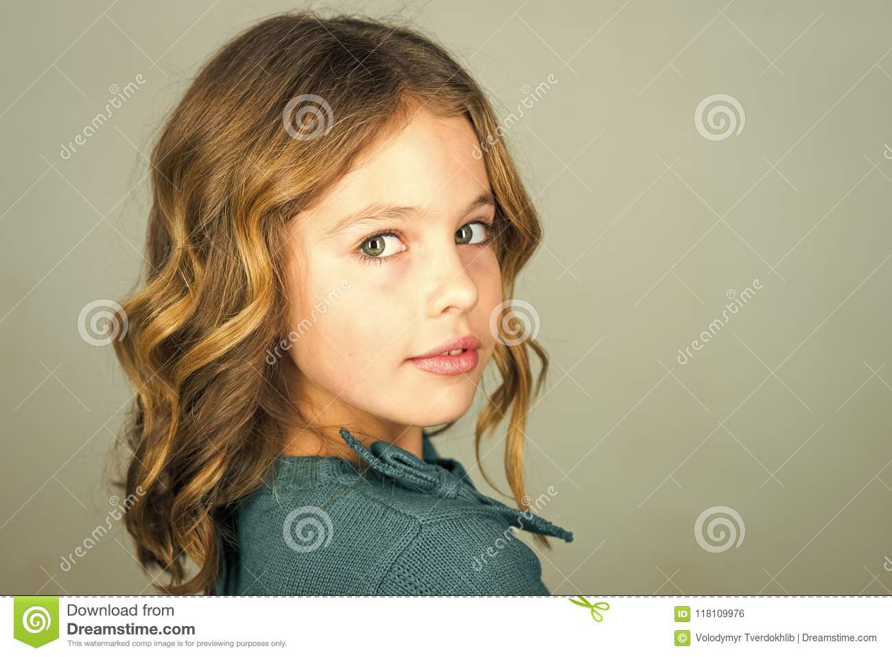 stylish cute kid posing on grey background. face kid for magazine