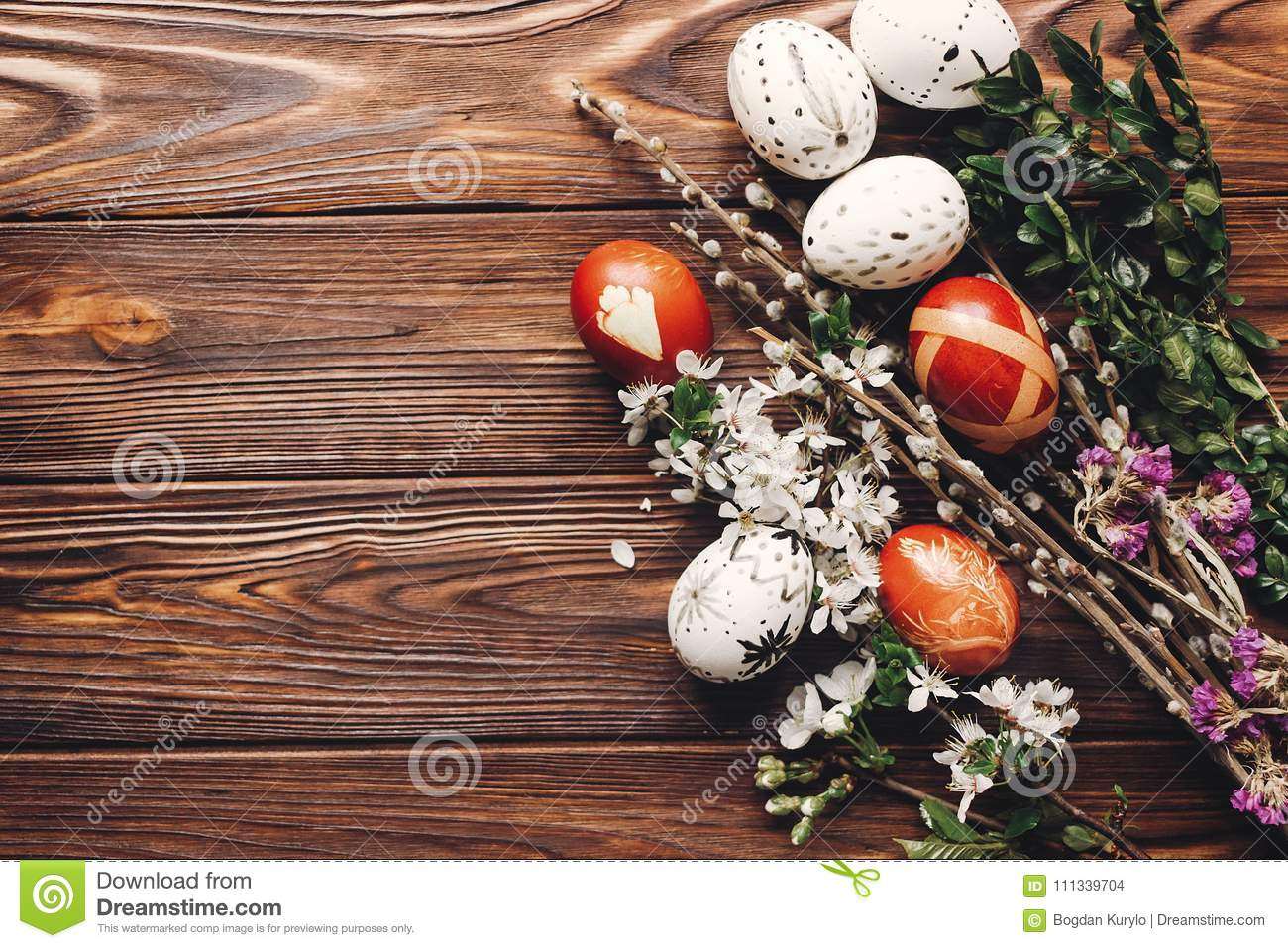 stylish easter eggs with white flowers and buds on wooden background flat lay. modern eggs and natural dyed with herbs, willow b