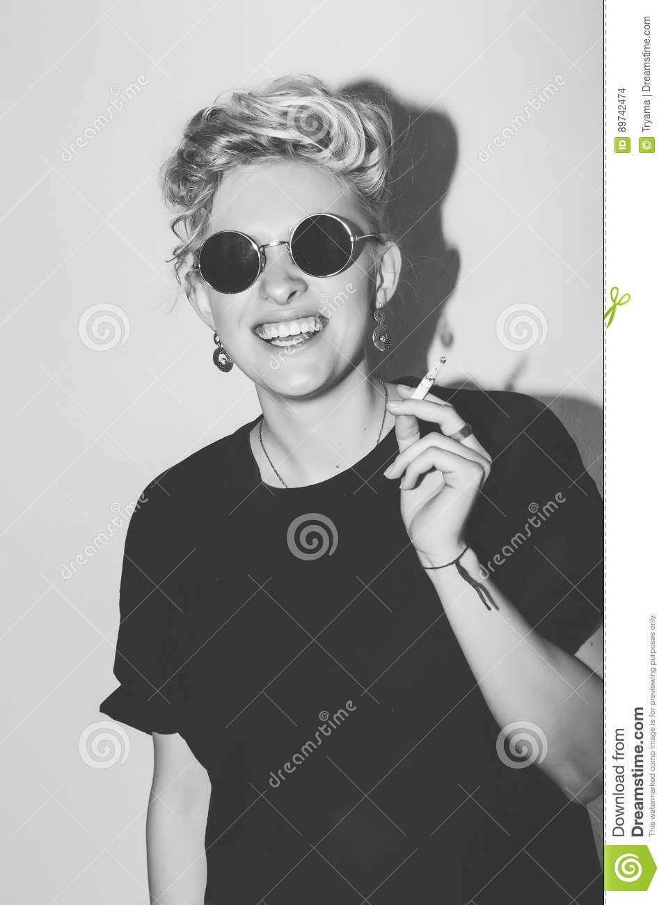 fd6c59efc80 Stylish fashion blonde bad girl in a black t-shirt and rock sunglasses.  Dangerous rocky emotional woman. Black and white toned. White background