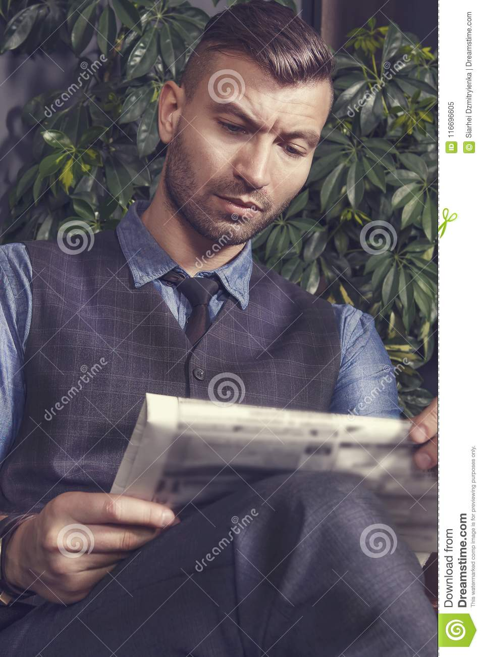 Stylish fashionable brutal handsome businessman sits in chair and reads news in newspaper. Portrait of man in suit