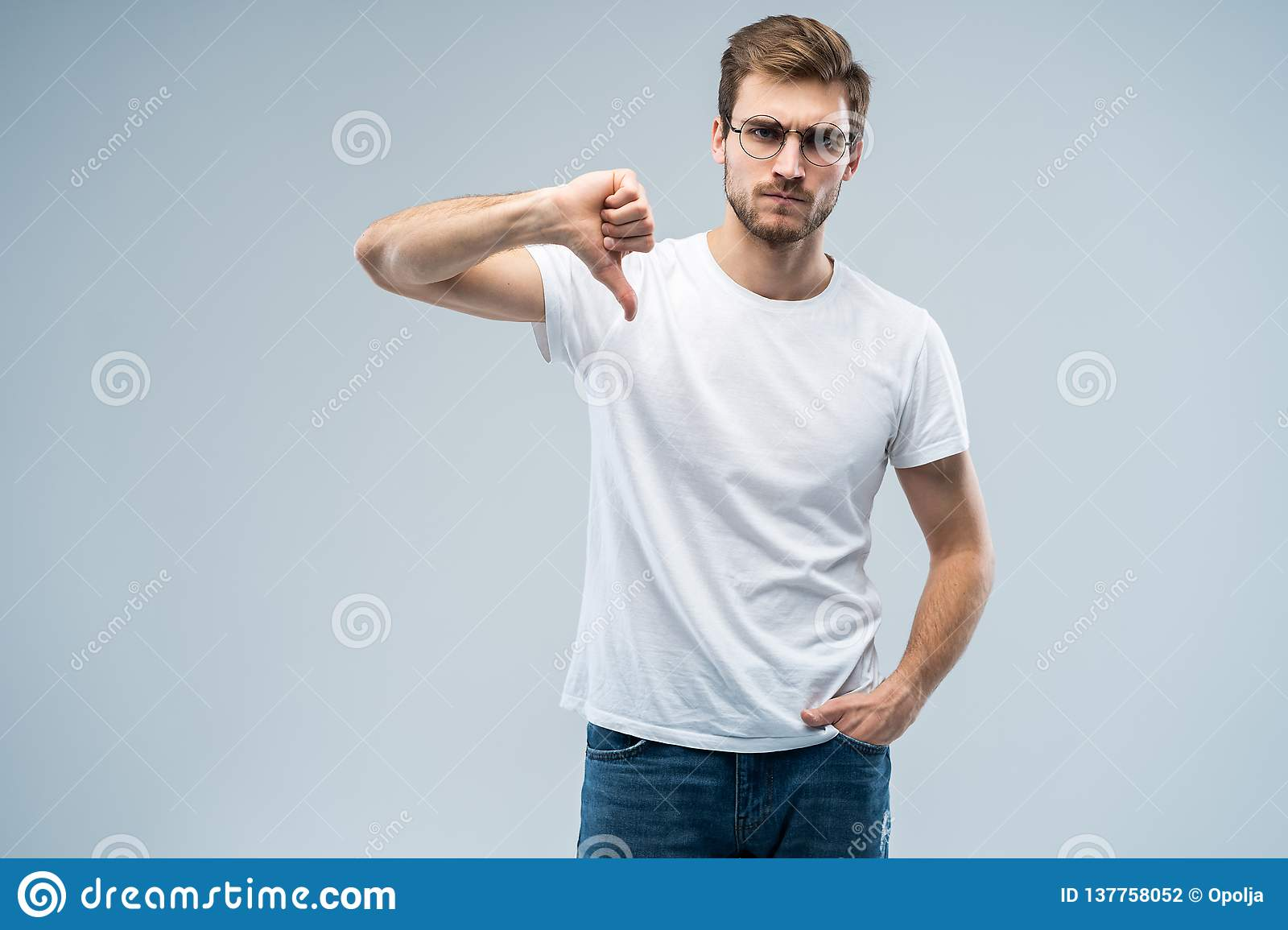 Stylish fashionable male poses indoors against gray background, assess project, shows sign of dislike, looks with
