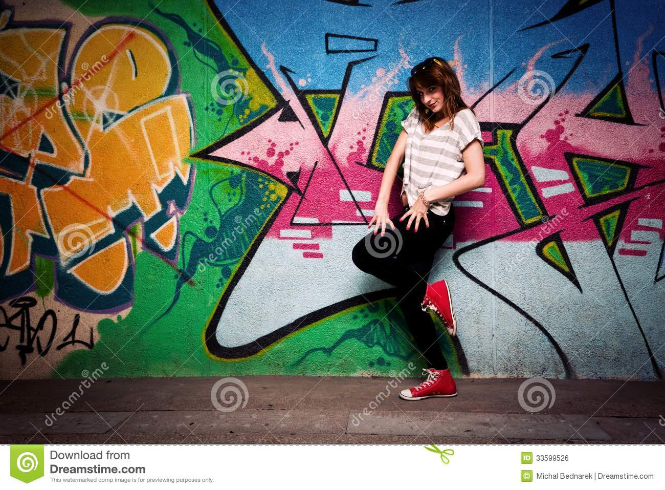 stylish girl in a dance pose against graffiti wall stock