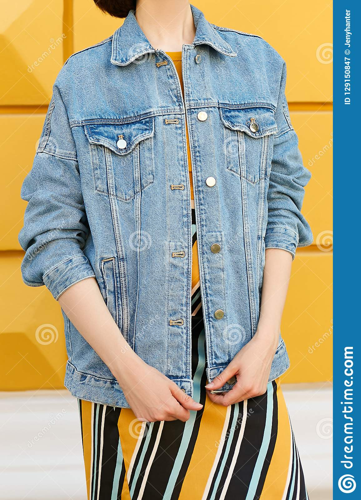 A stylish girl is dressed in a denim jacket and in a yellow skirt with an ornament stands straight. Street fashion.