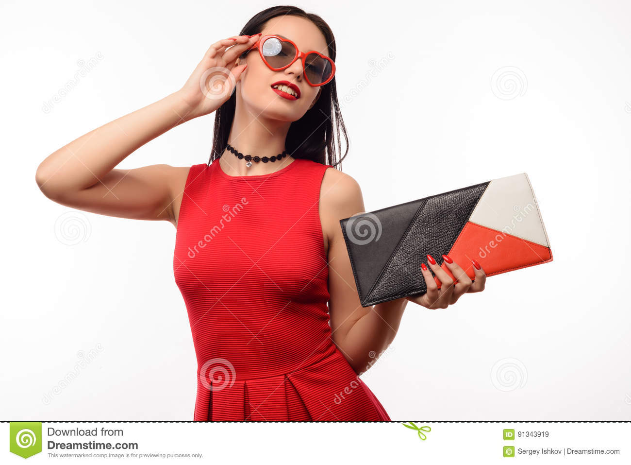 Stylish girl in red dress and clutch holds on to sunglasses in the shape of heart