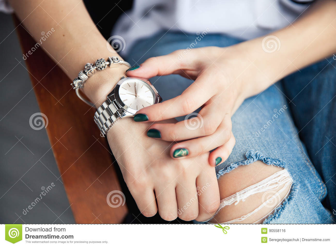 Stylish Girl Sitting In Torn Jeans And Green Modern Manicure ...