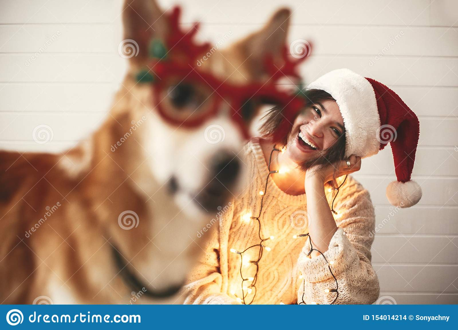 Stylish girl smiling in santa hat and christmas lights and looking at cute golden dog with funny emotions in festive reindeer