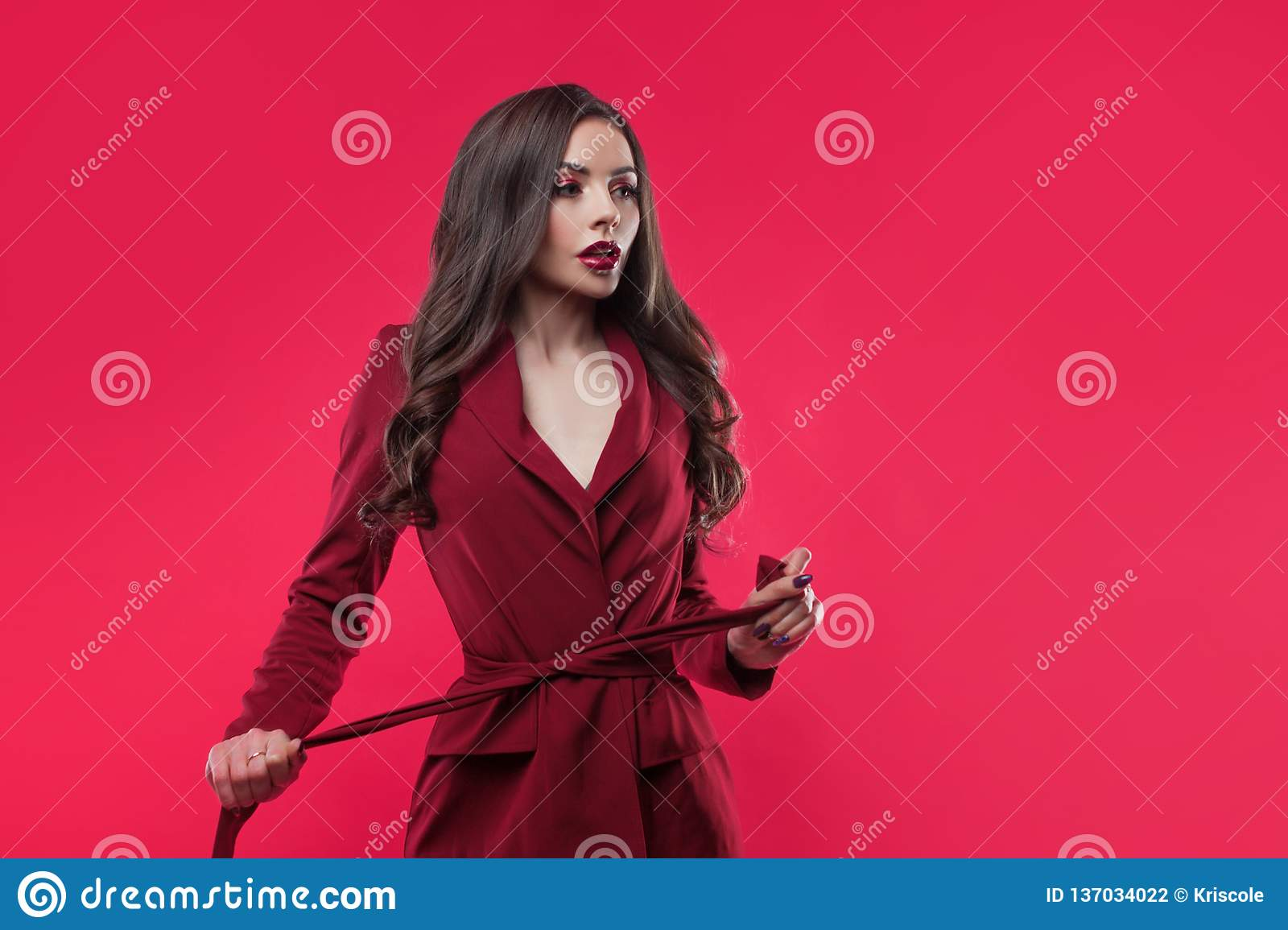Stylish glamorous girl tightens the belt. concept of diet and weight loss. Attractive young brunette