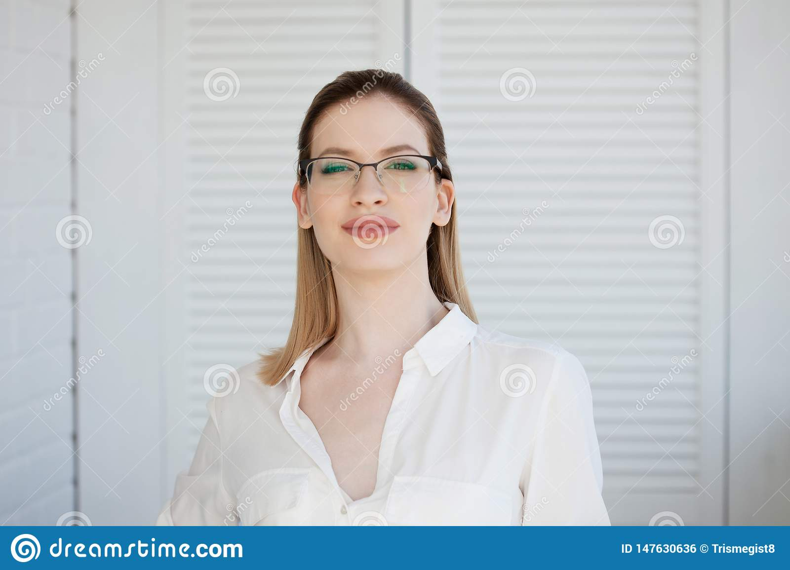 Stylish glasses in a thin frame, vision correction. Portrait of a young woman
