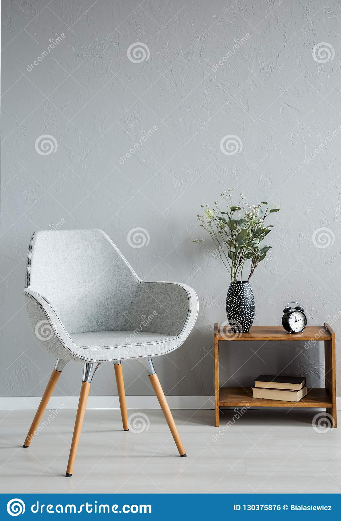 Stylish grey chair next to cabinet with vase and flowers in modern office interior, real photo