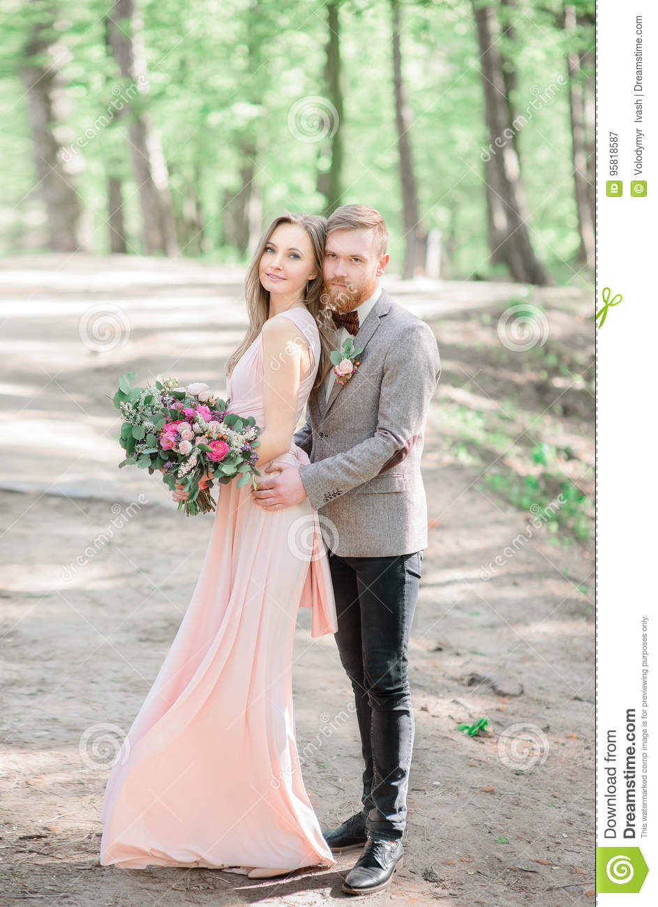Stylish Groom In Grey Jacket Hugs Pretty Bride In Pink Dress