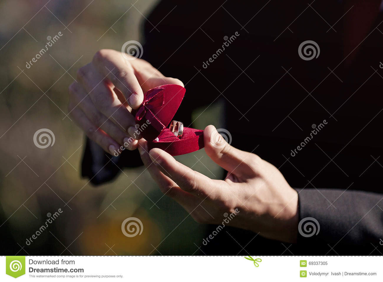 stylish groom is holding a pair of wedding rings in a cute heart - Cute Wedding Rings