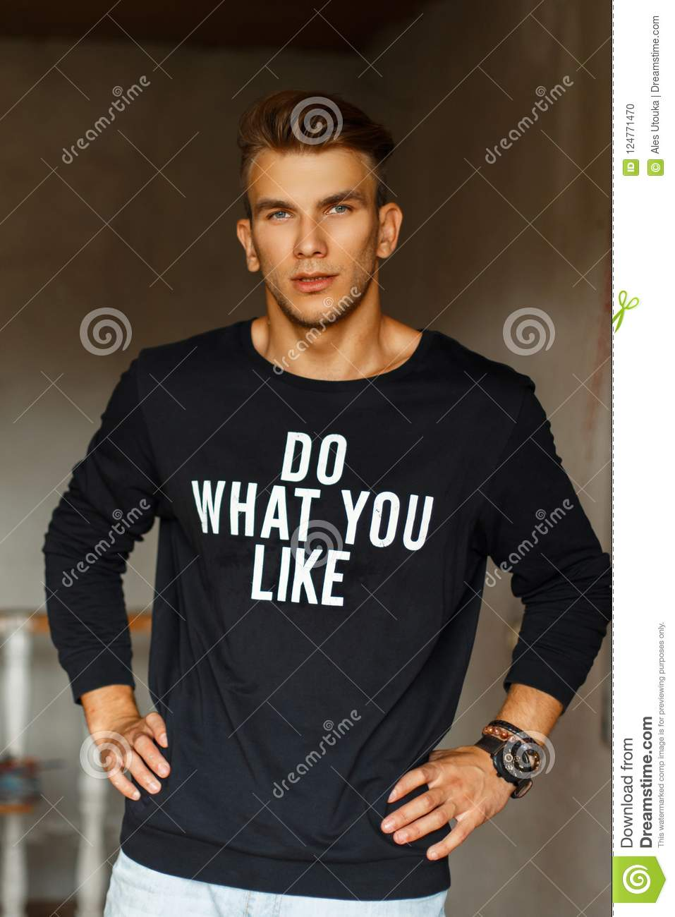 Stylish handsome young male artist in a black pullover with word