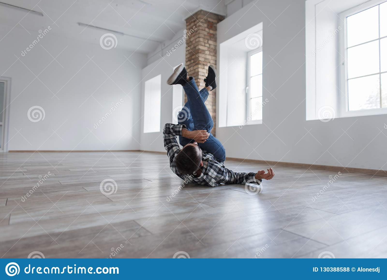 Stylish handsome young man in a shirt with jeans dancing break