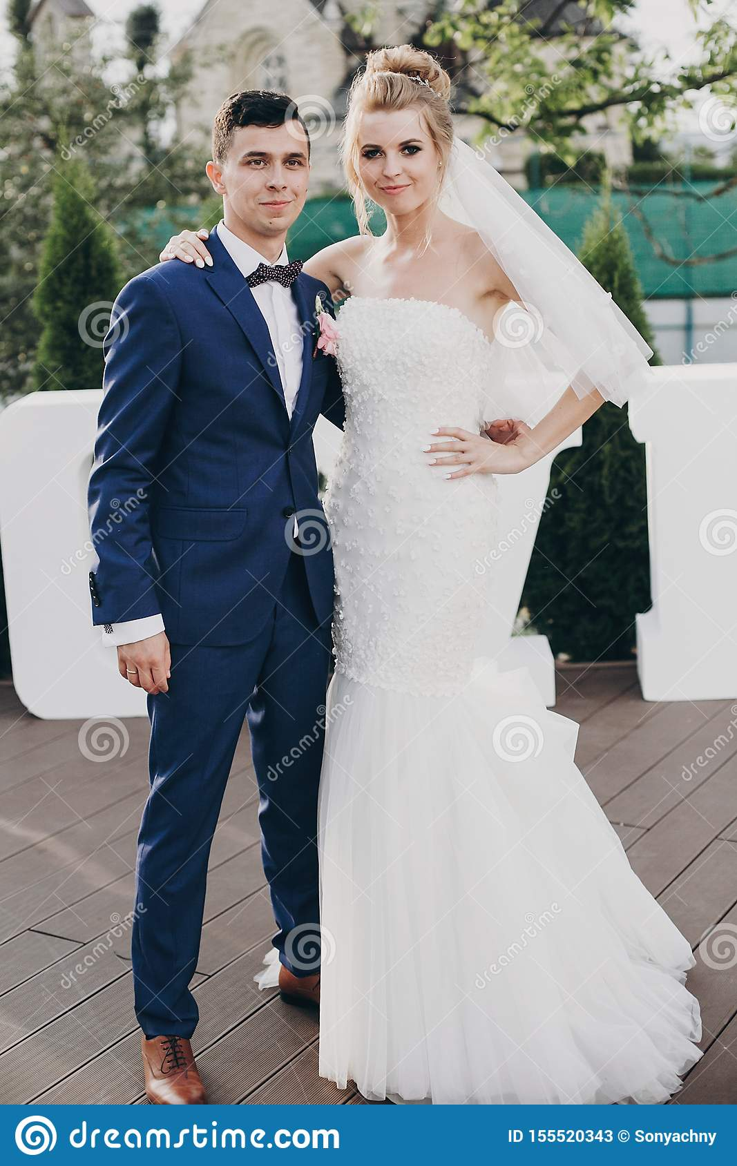 Stylish happy bride and groom posing at big love word in evening light at wedding reception outdoors. Gorgeous wedding couple of