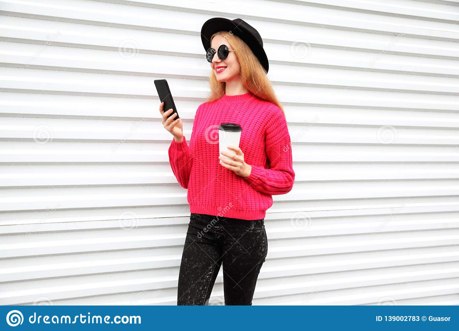 Stylish happy woman looking at phone holding coffee cup, female model wearing black round hat, pink knitted sweater in city