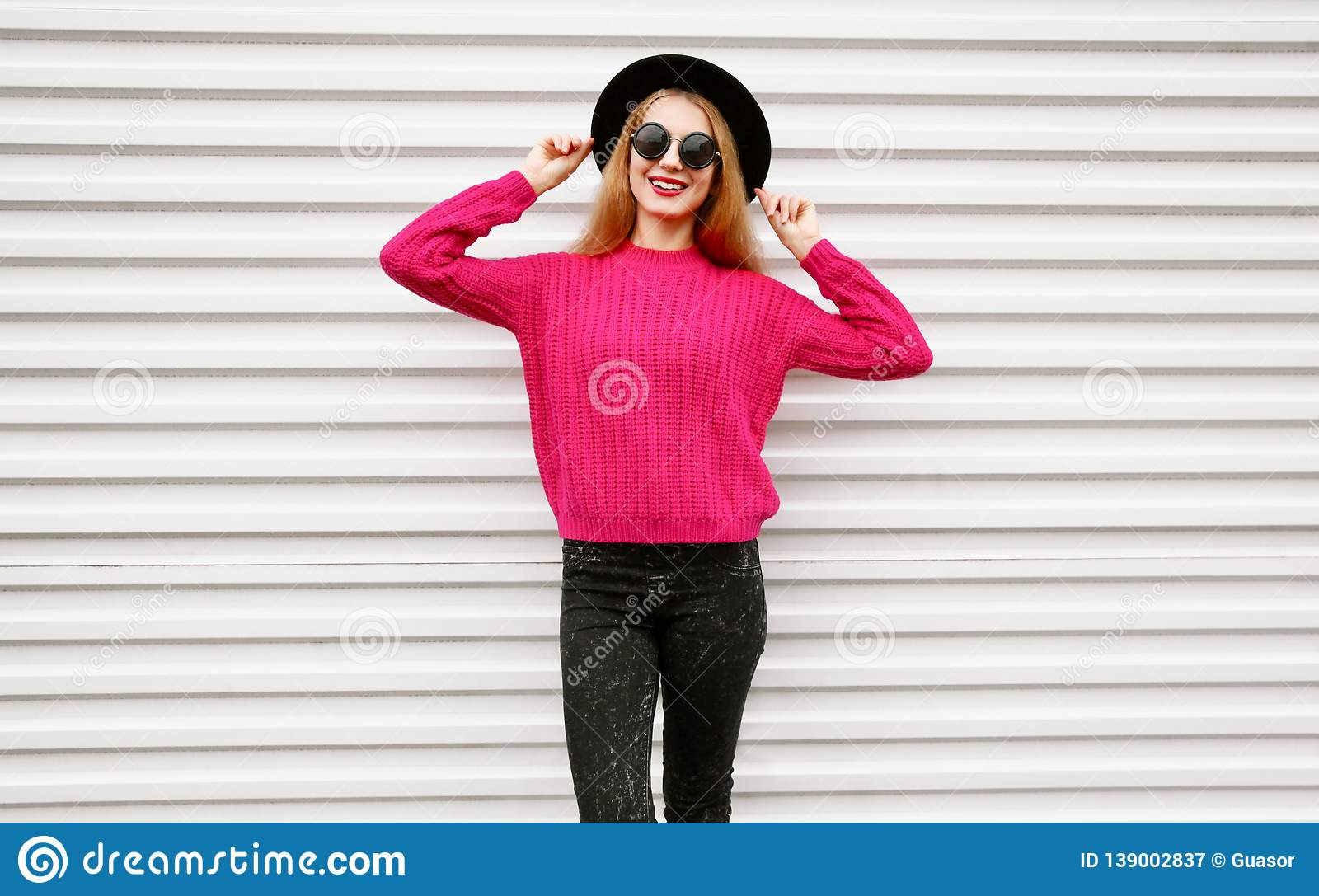 Stylish happy young woman in colorful pink knitted sweater, black round hat posing on city white wall