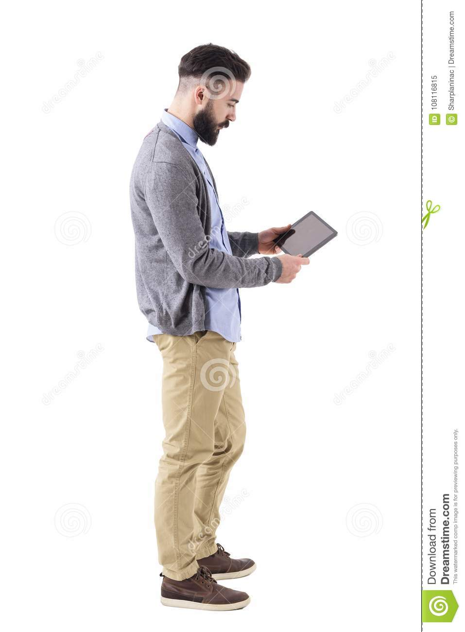Stylish hipster businessman holding and watching tablet pad computer. Side view.
