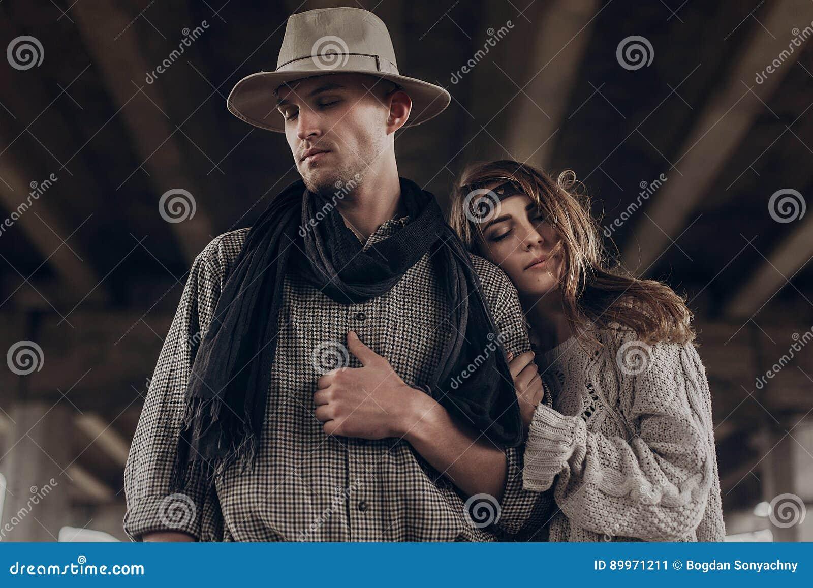 Stylish hipster couple dreaming under abandoned bridge. boho gyp