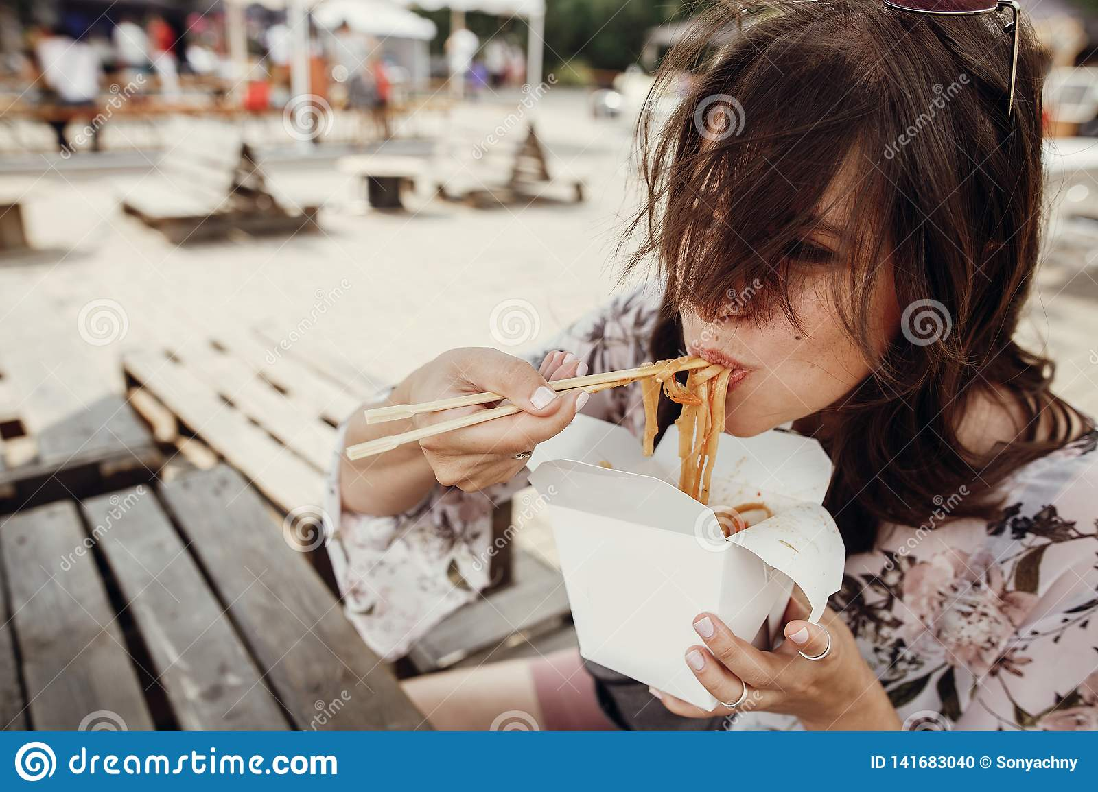 Stylish hipster girl eating wok noodles with vegetables and seafood from carton box with bamboo chopsticks. Asian Street food