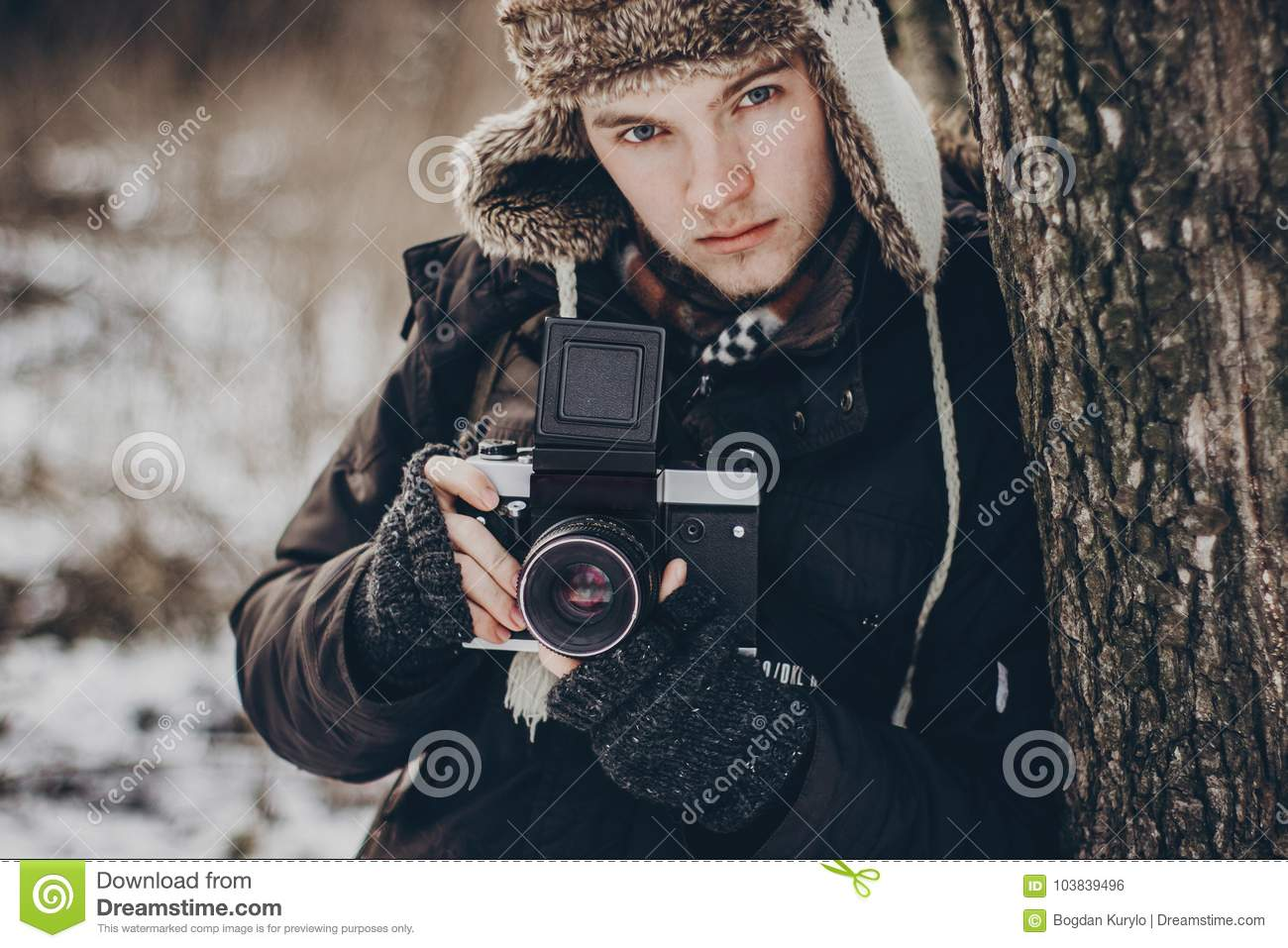 3c1b5110b0f Stylish hipster traveler man with old photo camera exploring in snowy woods in  winter. bearded guy portrait in cold forest. space for text. atmospheric ...
