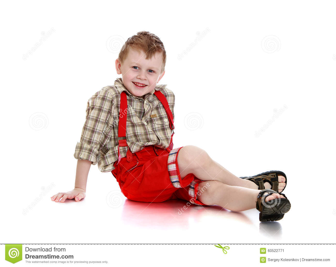 ad9f7e655 Happy little blond boy in a plaid shirt and red shorts with straps sitting  on the floor leaning on hands-Isolated on white background