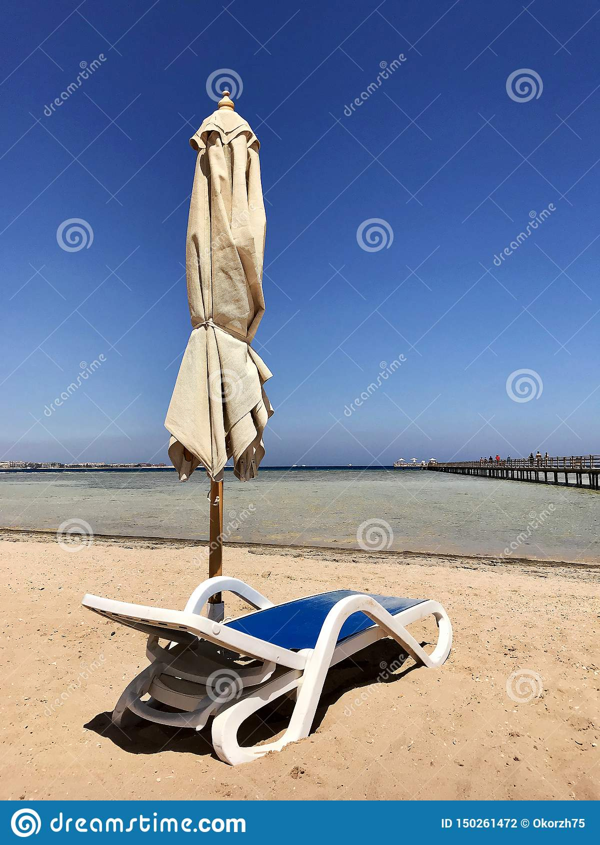 Stylish lounger in yellow sand to sun sunbed on beach in summer under open sky