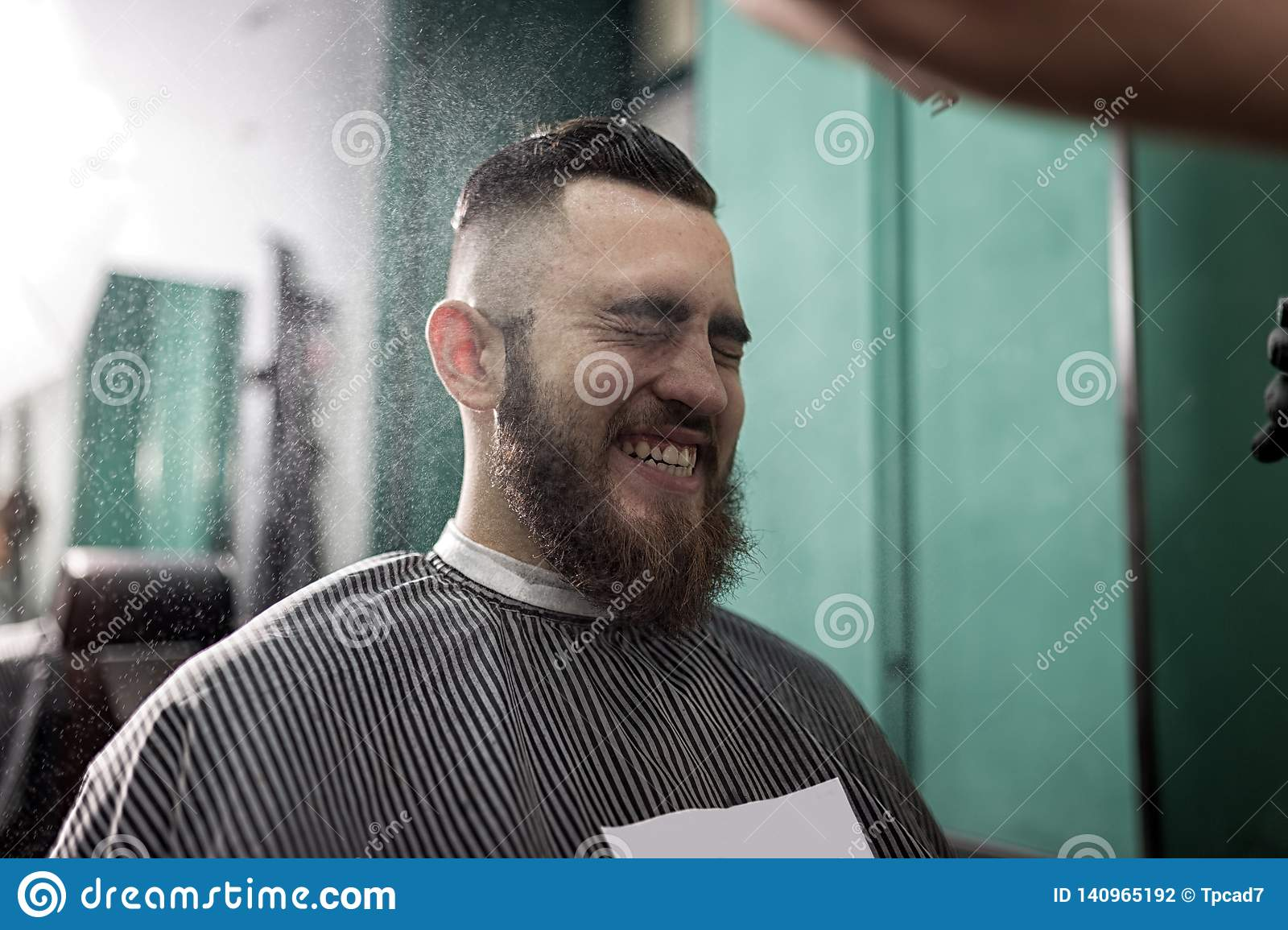 Stylish man with a beard sits and smiles at a barber shop. Barber in black gloves does the spraying for hairstyle