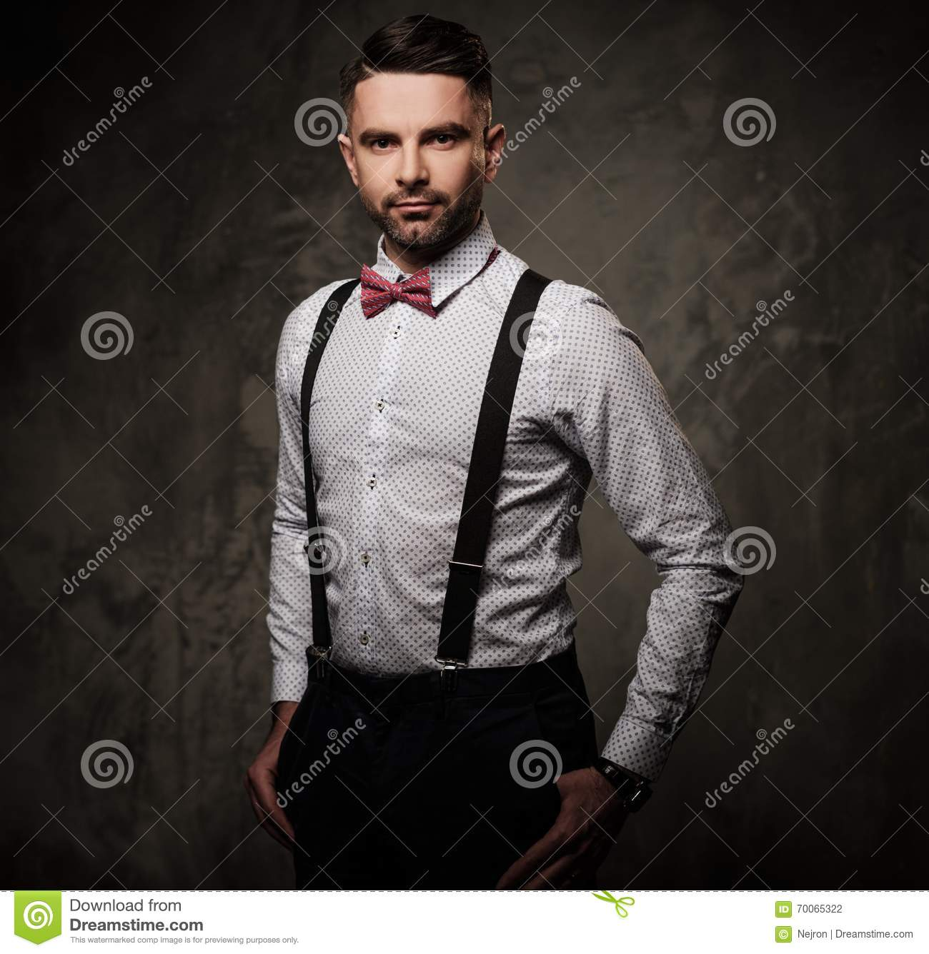 stylish man with bow tie wearing suspenders and posing on. Black Bedroom Furniture Sets. Home Design Ideas