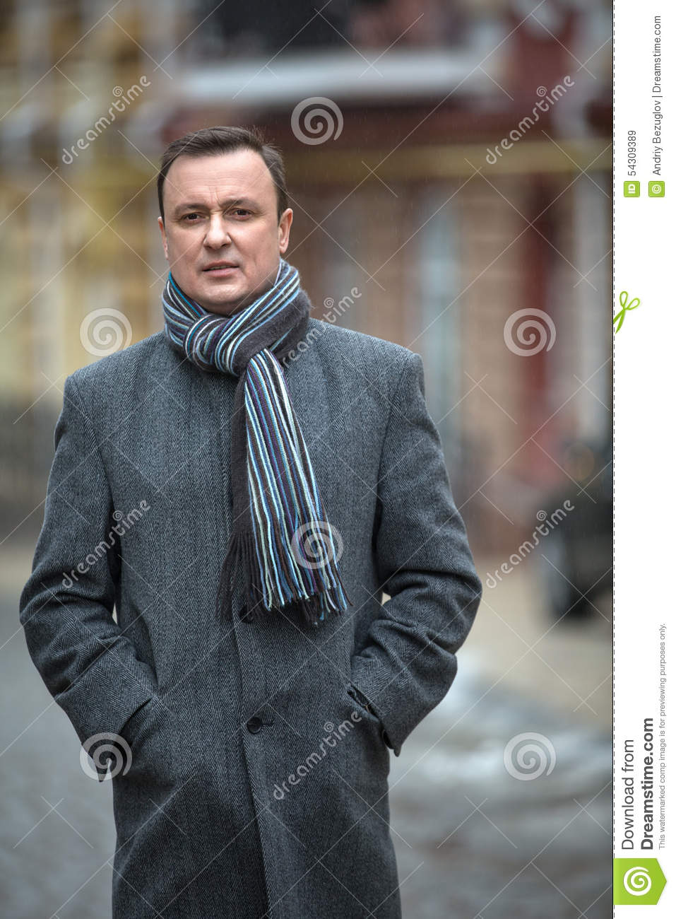 Stylish man in a gray coat with scraft on the