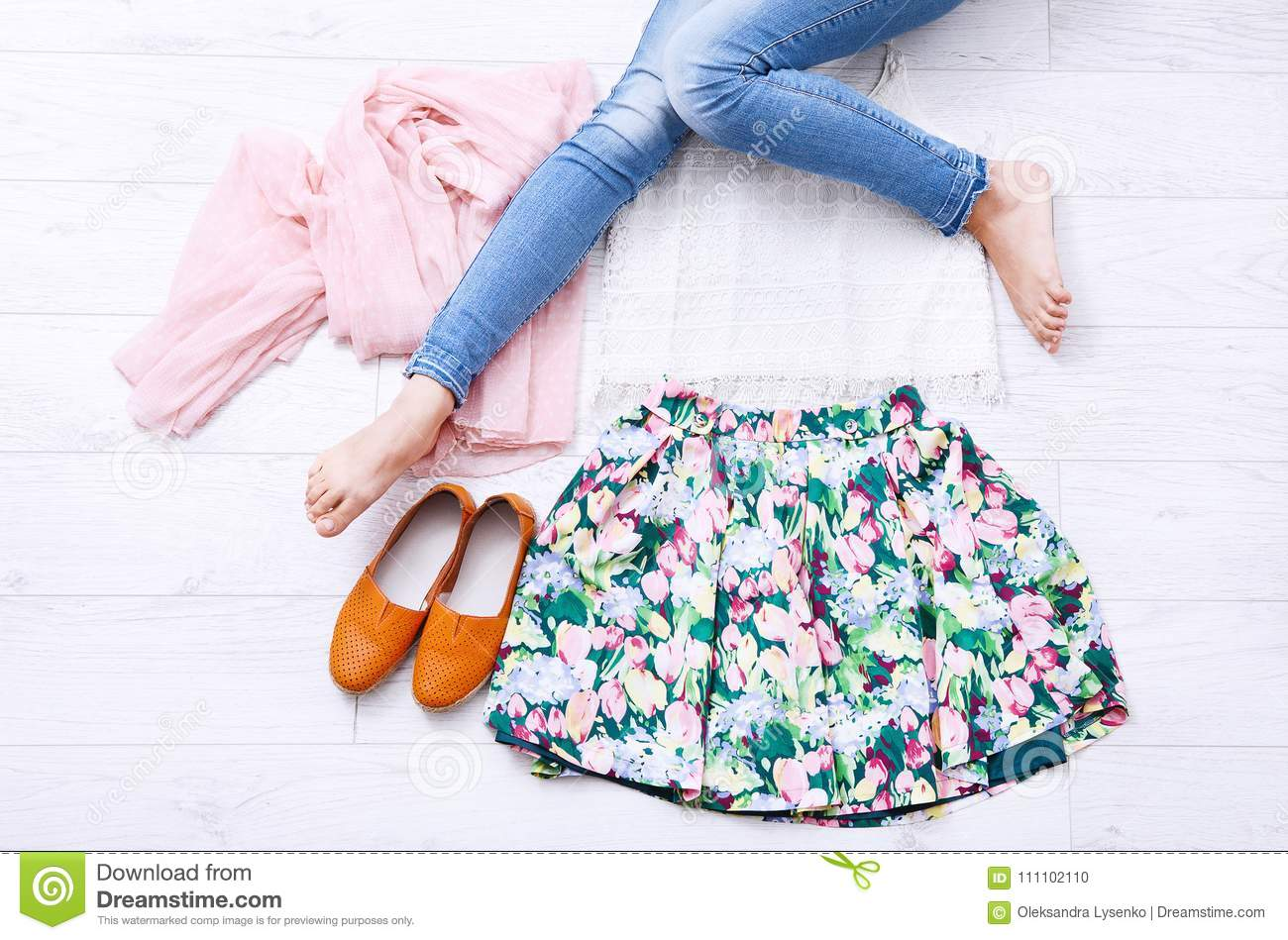 Stylish outfit with accessories and female legs on white wooden background. Top view and copy space. Mock up. Summer clothes