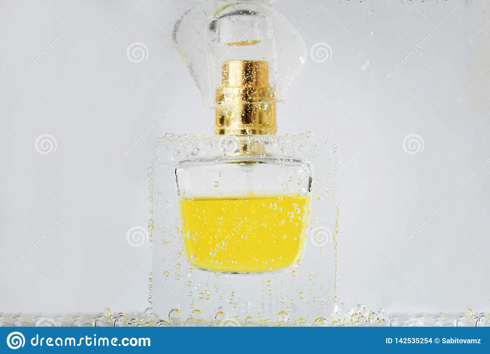 Stylish perfume bottle in water with bubbles